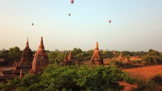 vidéos et rushes de aerial shot of hot air balloons flying over pagodas on sunny day, drone ascending over buddhist temples amidst trees against sky - bagan, myanmar - temple