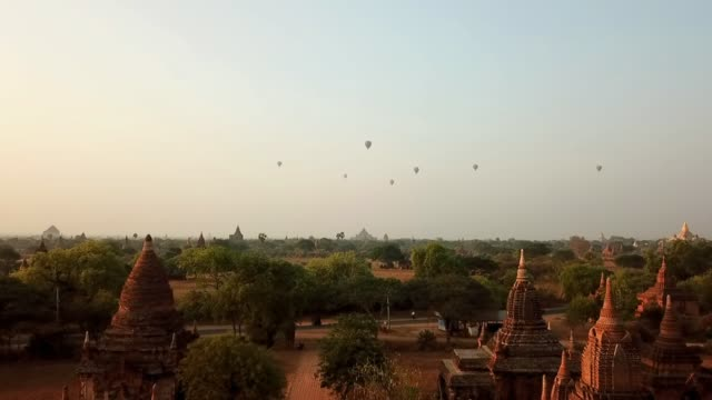 aerial shot of hot air balloons over pagodas and field, drone ascending forward over buddhist temples amidst trees against sky - bagan, myanmar - bagan stock videos & royalty-free footage