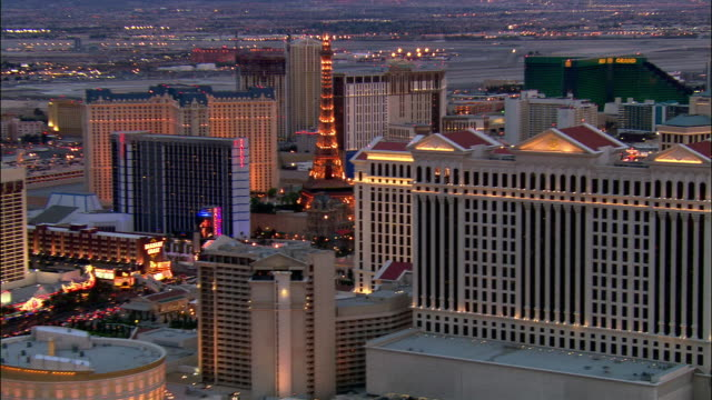 aerial shot of hotels and casinos on las vegas strip at dusk / las vegas, nevada - replica della torre eiffel video stock e b–roll