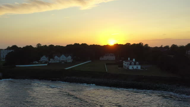 aerial shot of houses in city against orange sky, drone descending backward over sea at sunset - newport, rhode island - video stock videos & royalty-free footage