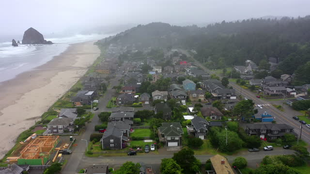 aerial shot of houses in city by beach against sky, drone ascending over residential district by sea - cannon beach, oregon - オレゴン沿岸点の映像素材/bロール