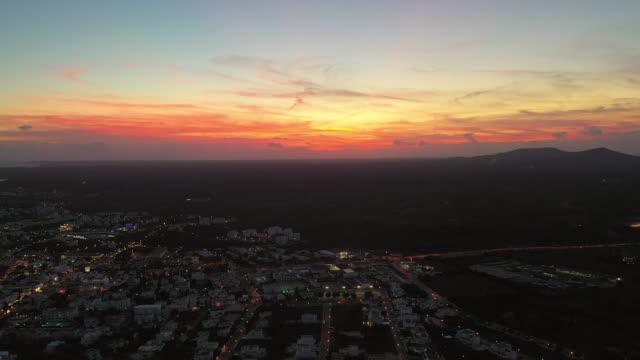 vídeos y material grabado en eventos de stock de aerial shot of illuminated city against sky during sunset, drone flying backward over landscape - cales de mallorca, spain - plano descripción física