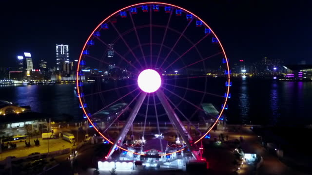 aerial shot of illuminated ferris wheel by sea in city at night, drone flying backward from structure against sky - hong kong, china - big wheel stock videos & royalty-free footage