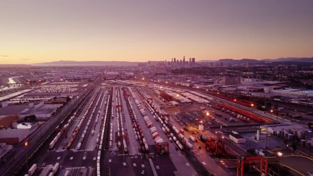 aerial shot of intermodal rail yard with downtown los angeles skyline - unloading stock videos & royalty-free footage