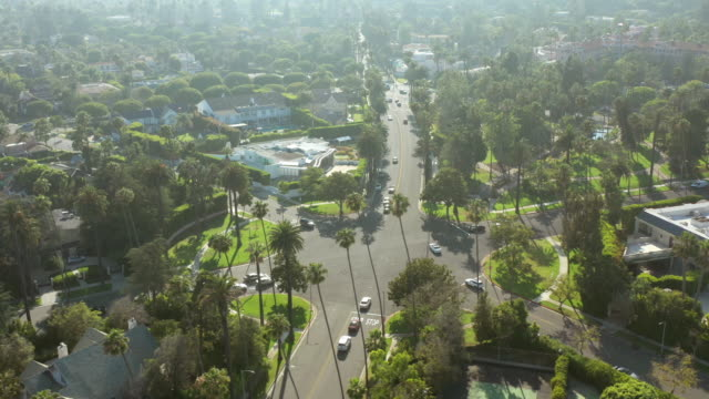stockvideo's en b-roll-footage met aerial shot of intersection in beverly hills lined with palm trees - beverly hills californië