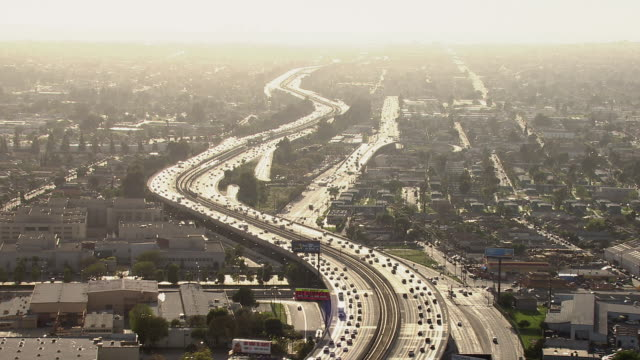 aerial shot of interstate freeway curving through a hazy los angeles landscape. - beliebiger ort stock-videos und b-roll-filmmaterial
