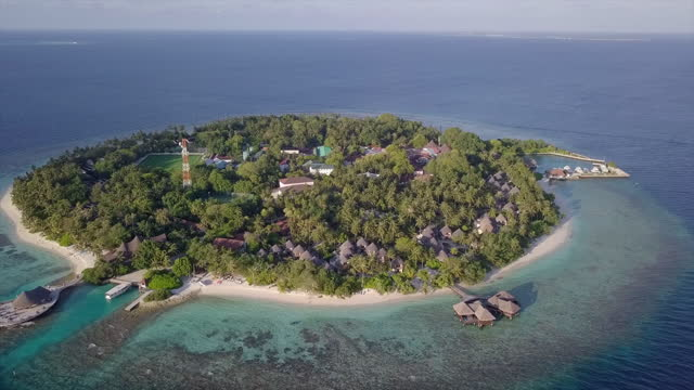 aerial shot of island with green trees against sky, drone ascending backward over turquoise sea on sunny day - bandos, maldives - yacht stock videos & royalty-free footage