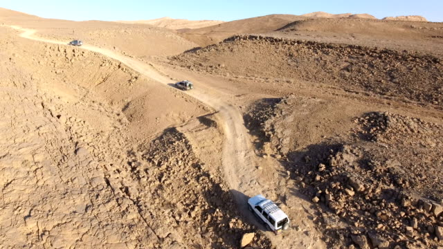 aerial shot of jeep driving in makhtesh ramon, negev desert, israel - naher und mittlerer osten stock-videos und b-roll-filmmaterial