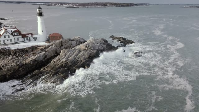 Aerial Shot of Lighthouse and Waves Hitting Rocky Cliffs