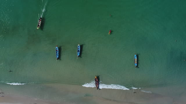 aerial shot of long tail boats on the beach. - phuket stock videos & royalty-free footage