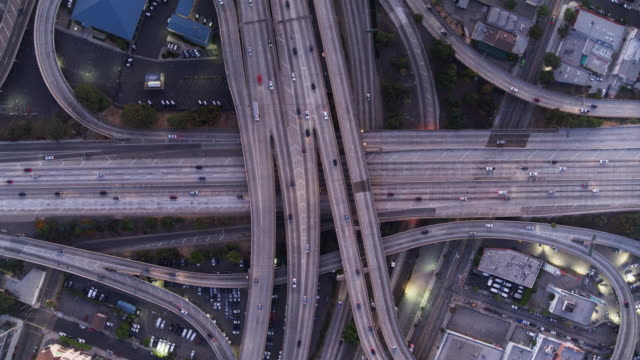 aerial shot of los angeles freeways at sunset - raccordo autostradale video stock e b–roll