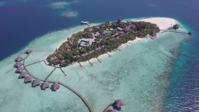 aerial shot of luxurious resort island on sea during sunny day, drone flying forward over water bungalows - vaadhoo, maldives - island stock videos & royalty-free footage