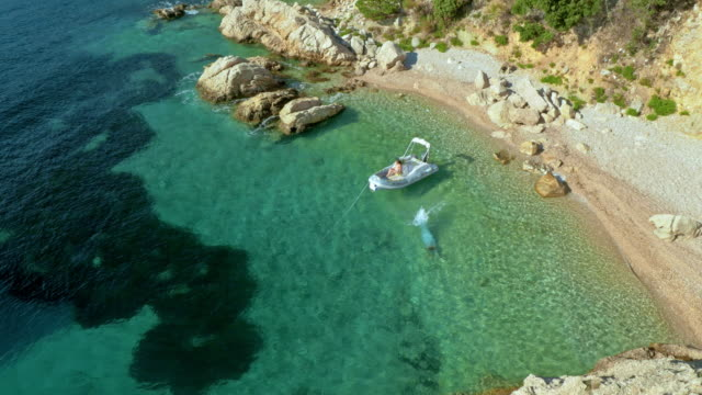 Aerial shot of man swimming in bay near his boat