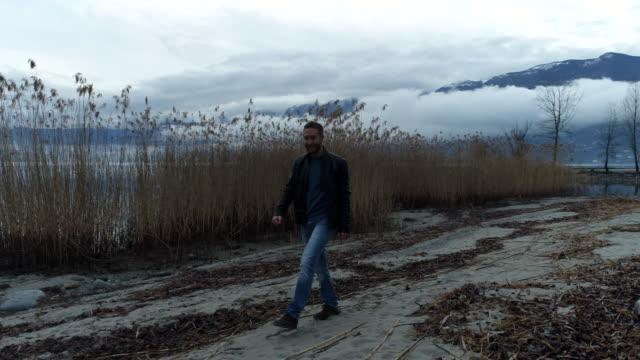 湖のそばに歩いてくる男性の空中ショット - リフレクション湖点の映像素材/bロール