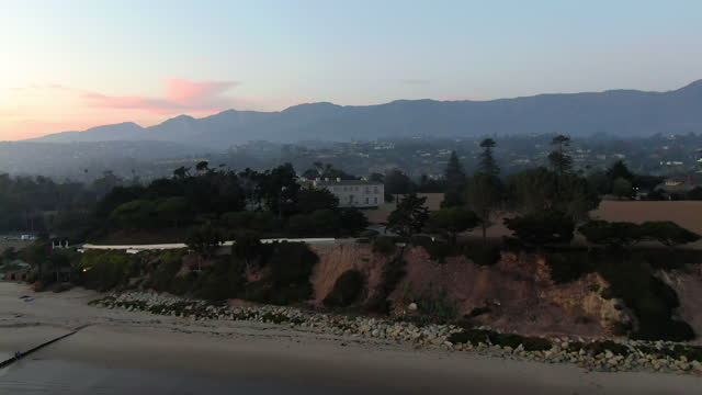 aerial shot of mansion amidst trees at butterfly beach, drone flying backward over waves splashing on shore against sky at sunset - santa barbara, california - mansion stock videos & royalty-free footage