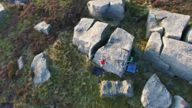 aerial shot of men climbing boulders while bouldering. - masso video stock e b–roll