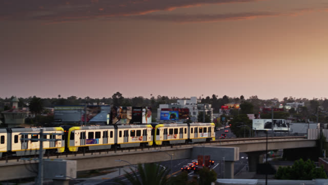 vidéos et rushes de aerial shot of metro expo line train in west los angeles at sunset - los angeles county