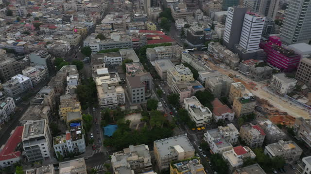 aerial shot of modern buildings at downtown against sky, drone flying over vehicles on street by skyscrapers in city at sunset - tel aviv, israel - aerial stock videos & royalty-free footage