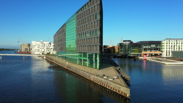 aerial shot of modern buildings by canal in city against sky, drone ascending over sea on sunny day - copenhagen, denmark - オーレスン地域点の映像素材/bロール