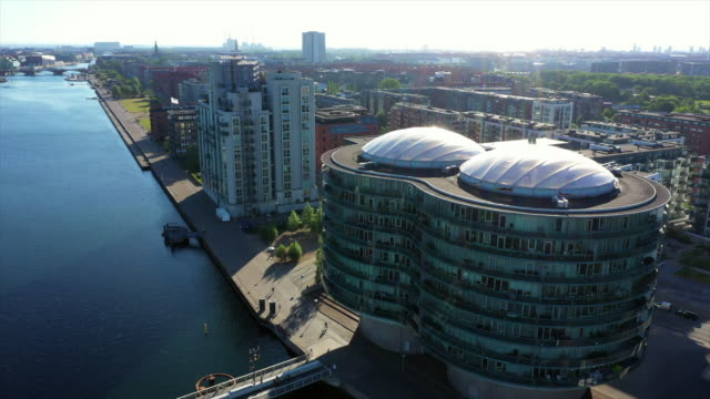 aerial shot of modern residential building by sea canal in city, drone descending over bridge against sky on sunny day - copenhagen, denmark - copenhagen stock videos & royalty-free footage