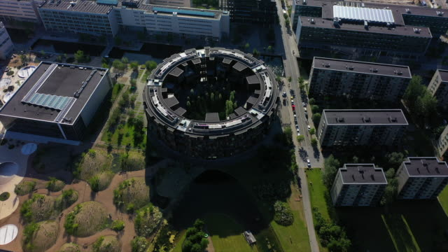aerial shot of modern residential college building in city, drone descending over street with vehicles on sunny day - copenhagen, denmark - copenhagen stock videos & royalty-free footage