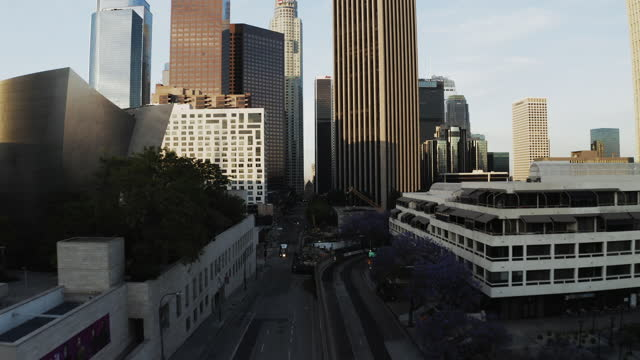 aerial shot of modern skyscrapers at downtown against sky, drone flying forward over city at sunset - los angeles, california - los angeles county stock-videos und b-roll-filmmaterial