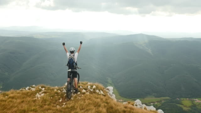 Aerial shot of mountain biker on top with hands raised