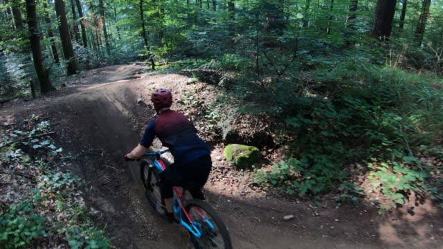 aerial shot of mountain bikers descending a mountain trail through the forest - mountain biking stock videos & royalty-free footage