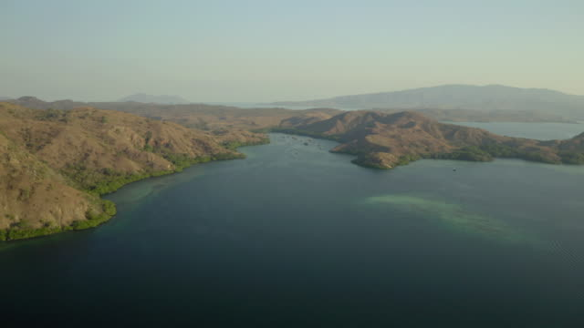 aerial shot of mountain by sea with boats against blue sky, drone ascending over ocean on sunny day - komodo island, indonesia - komodo island stock videos & royalty-free footage