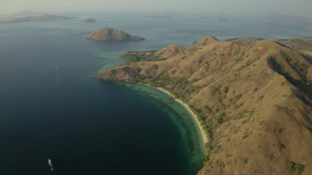 aerial shot of mountain range by sea with boats during sunny day, drone flying forward over nautical vessels against sky - komodo island, indonesia - komodo island stock videos & royalty-free footage