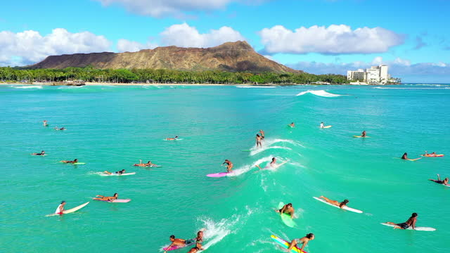aerial shot of mountains by beach against cloudy sky, people surfing in ocean during vacation - oahu, hawaii - hawaii islands stock videos & royalty-free footage