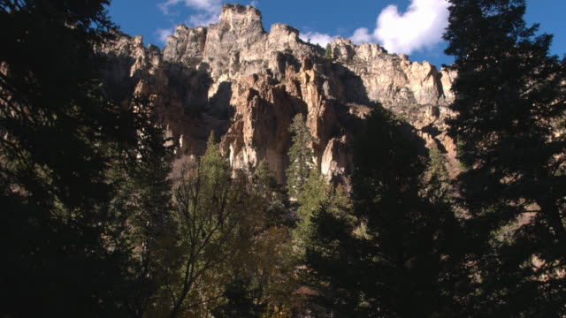 Aerial shot of mountainside cliff formations up a canyon