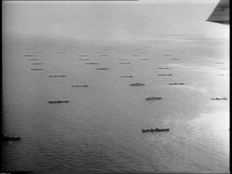 vídeos de stock, filmes e b-roll de aerial shot of navy fleet convoy of ships sailing on open water for the western front plane flying above / one ship then closer view of soldiers on... - paramount building