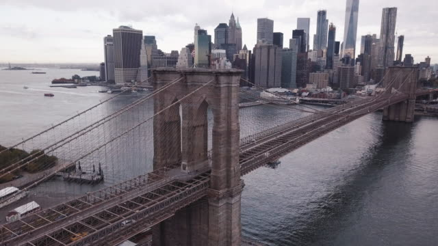 aerial shot of new york city's brooklyn bridge and lower manhattan on a cloudy autumn morning. - brooklyn bridge bildbanksvideor och videomaterial från bakom kulisserna