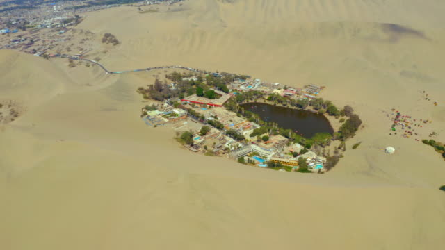 aerial shot of oasis by buildings amidst sand dunes, drone panning over lagoon in desert village - huacachina, peru - peru stock videos & royalty-free footage