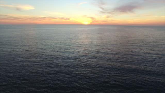 vídeos de stock, filmes e b-roll de aerial shot of ocean and beach city as the sun sets. - goodsportvideo