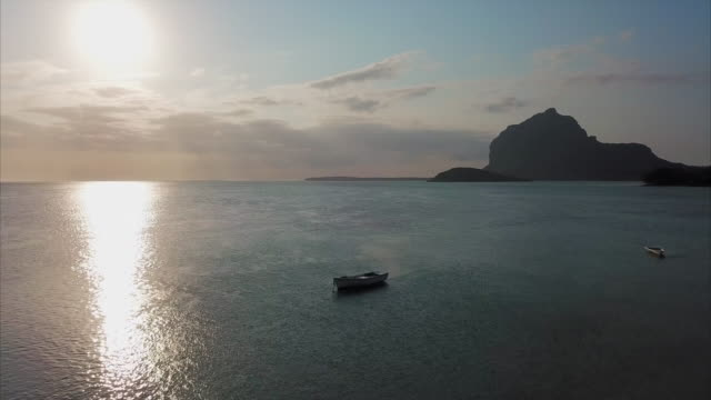 aerial shot of ocean near sunset reverses to reveal lone fishing boat - mauritius island, mauritius - anchored stock videos & royalty-free footage