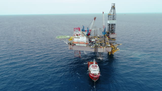 aerial shot of off shore oil platforms working close up day time - oil exploration platform stock videos & royalty-free footage