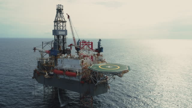 aerial shot of off shore oil platforms working close up day time - essential oil stock videos & royalty-free footage