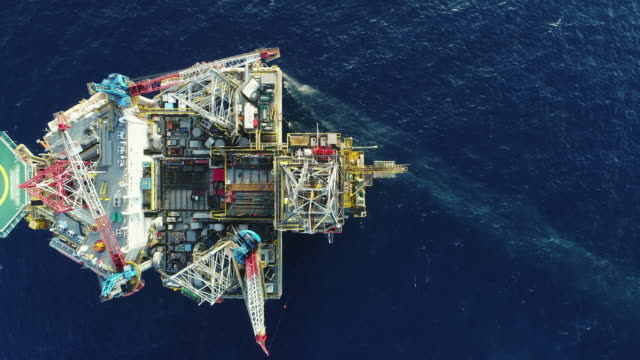 aerial shot of off shore oil platforms working close up day time - oil rig boat stock videos & royalty-free footage