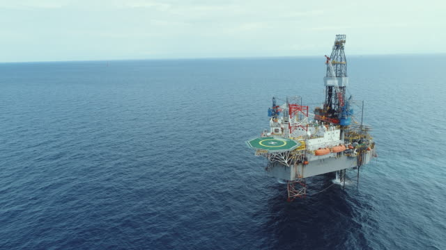 aerial shot of off shore oil platforms working close up day time stock video - pipeline stock videos & royalty-free footage