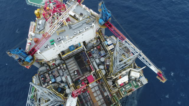 aerial shot of off shore oil platforms working close up day time stock video - drill stock videos & royalty-free footage