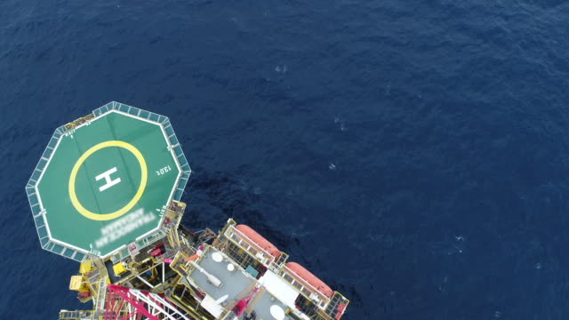 aerial shot of off shore oil platforms working close up day time - offshore platform stock videos & royalty-free footage