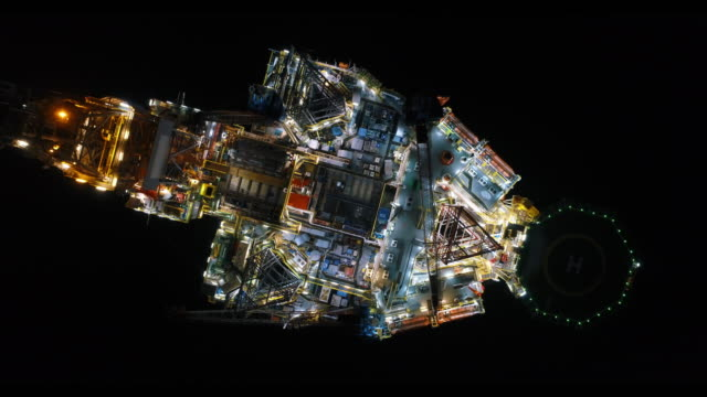 aerial shot of off shore oil platforms working close up night time - oil rig boat stock videos & royalty-free footage