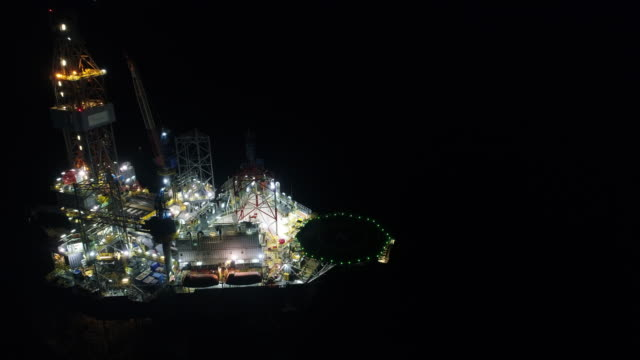aerial shot of off shore oil platforms working close up night time - oil exploration platform stock videos & royalty-free footage