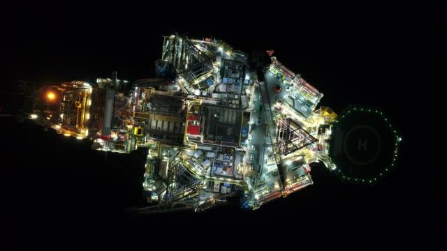 vídeos y material grabado en eventos de stock de toma aérea de plataformas petrolíferas off shore que trabajan de cerca por la noche - industria petrolera