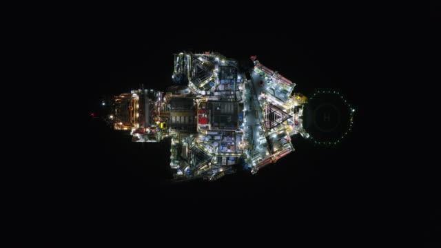 vidéos et rushes de tir aérien des plates-formes pétrolières outre-côte travaillant de près vers le haut du temps de nuit - navire