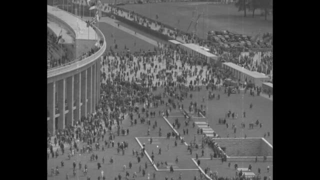 Aerial shot of Olympiastadion Berlin / high angle view of crowds milling around outside stadium / close up American Olympian crouched at the starting...