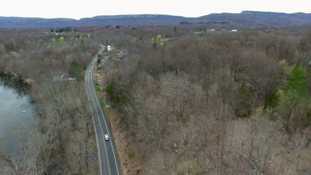 Aerial shot of one lane road winding along a rocky river toward a small town