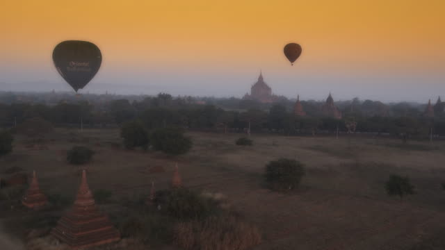 Aerial shot of pagodas and hot air balloons in Myanmar